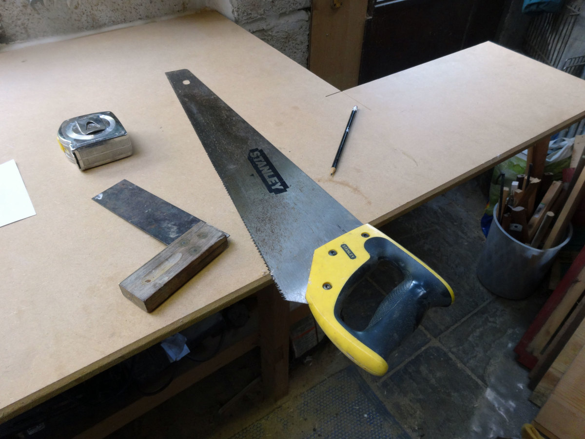 Use the back of the saw as a square to mark the straight edge of the shelf with a pencil.