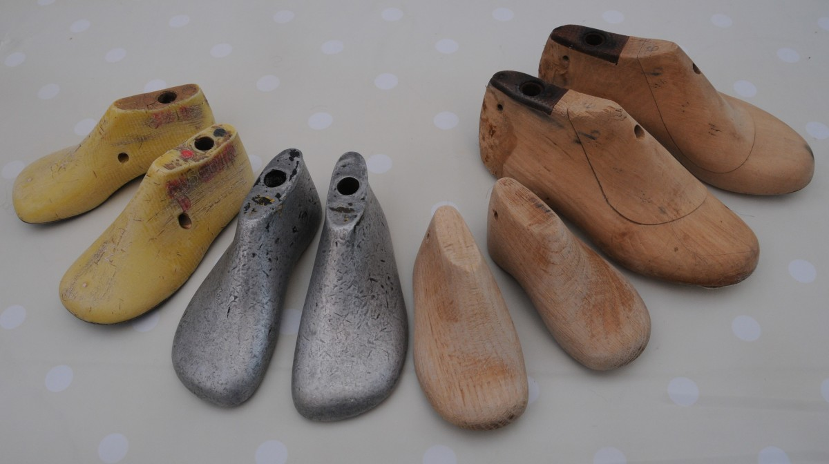 A group of children's size metal and wooden shoe lasts.