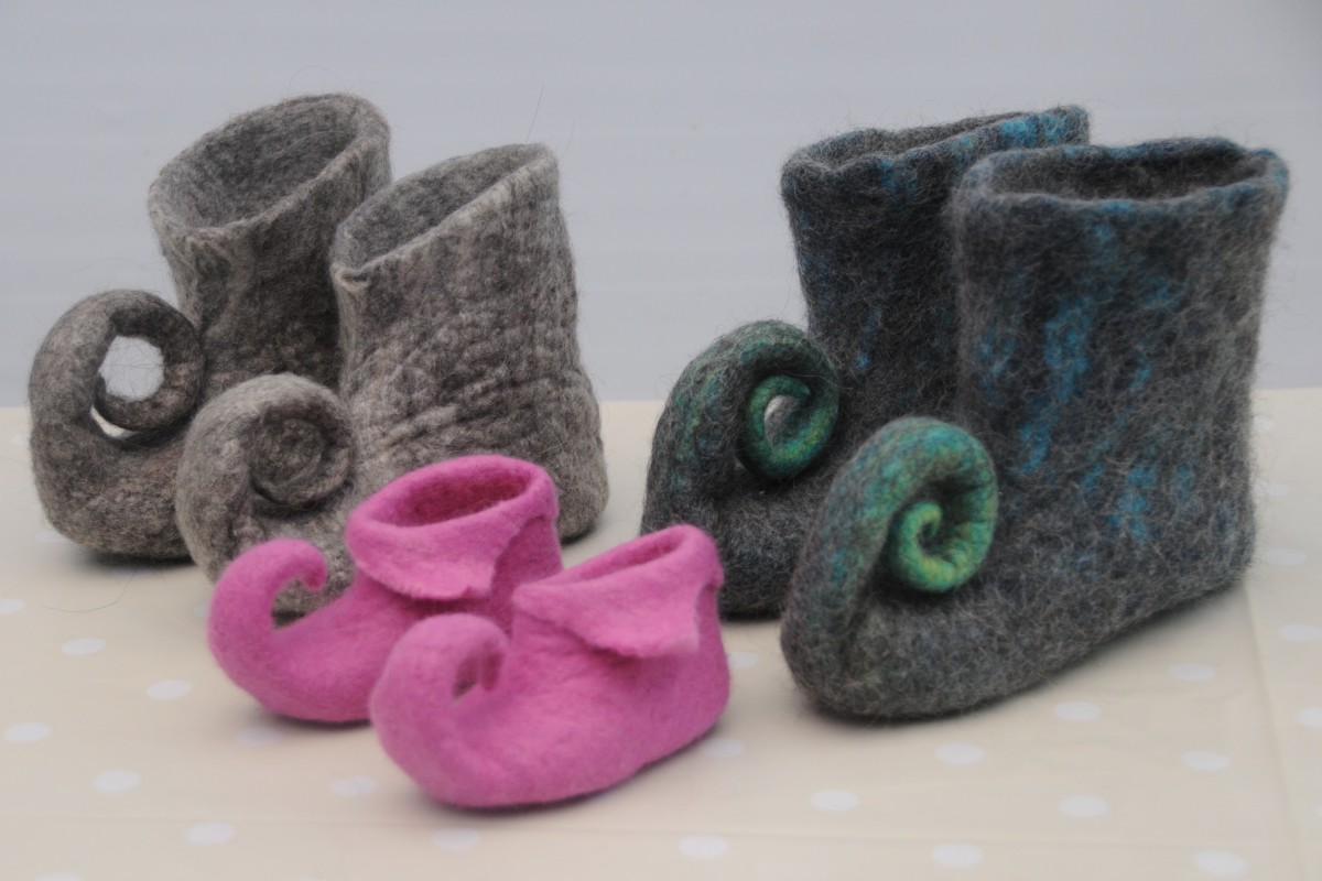 A group of Wet Felted Pixie Slippers.  The larger pairs of slippers were made with 3 layers of wool on both sides.  The pink pair were made using 2 layers of wool.