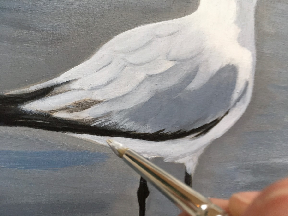 Painting fine detail on the bottom edge of the seagull's wing feathers.
