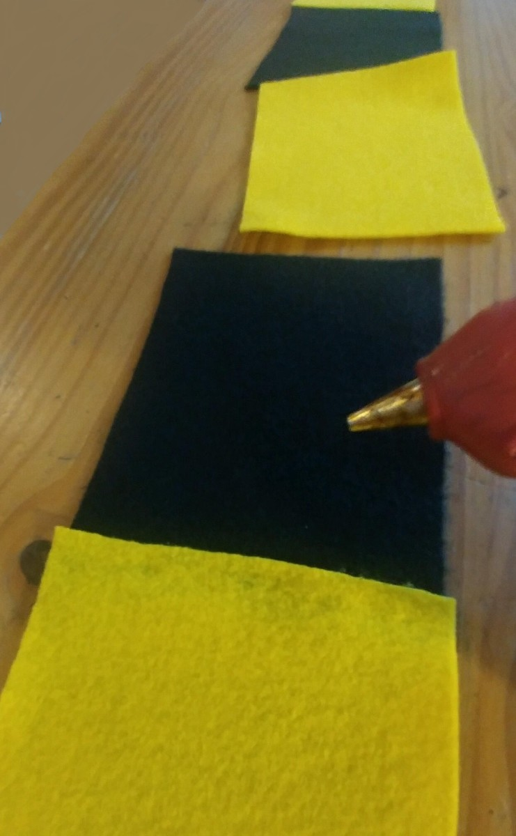 Use a glue gun to apply the glue on the edge of the felt sheets to glue together. It will dry quickly, so be sure to have in place, and press down on sheets with pressure to attach properly.