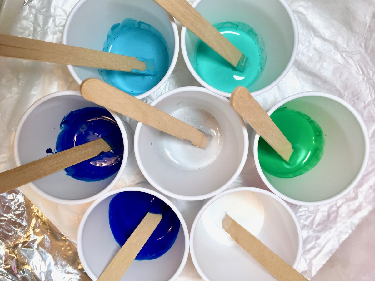 Plastic cups filled with pouring medium and paint.