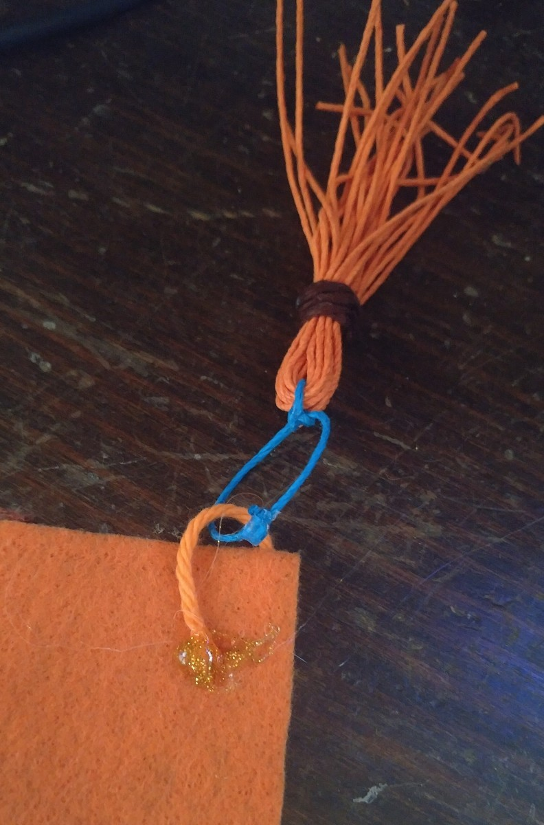 Tassel slipped onto yarn and glued in place.