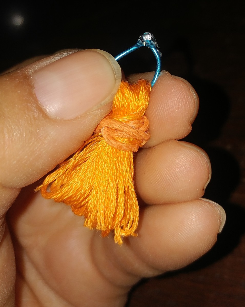 You can simply slip thread through and tie. I used jewelry wire to slip into top of tassel. I hot glued wire together, and turned it inside, to hide glue spot.