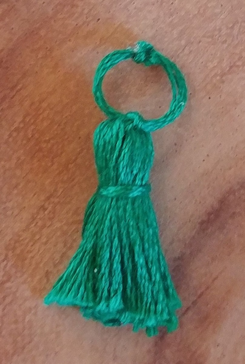 Tiny tassels can be made exactly as large ones, except downsized. This one is made without embelishments, strictly out of thread.