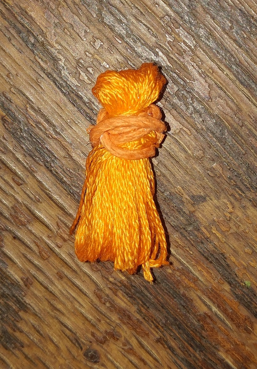 Wrap tie cord around tassel. Tie cord may be glued over knot.