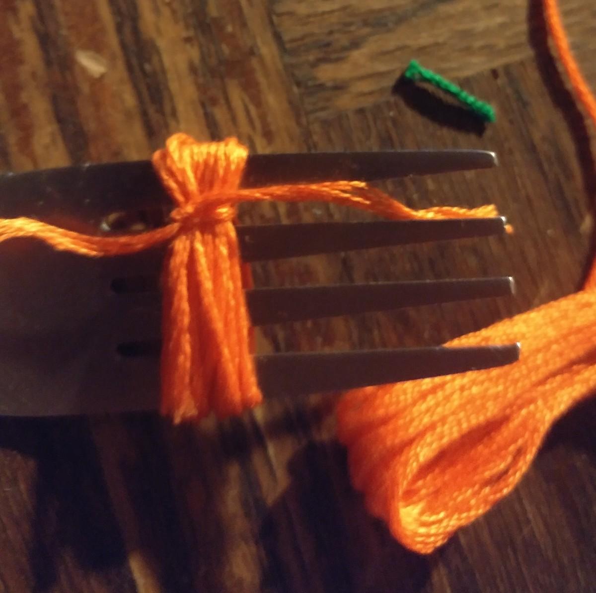 Slip thread through fork to tie knot around top of tassel.