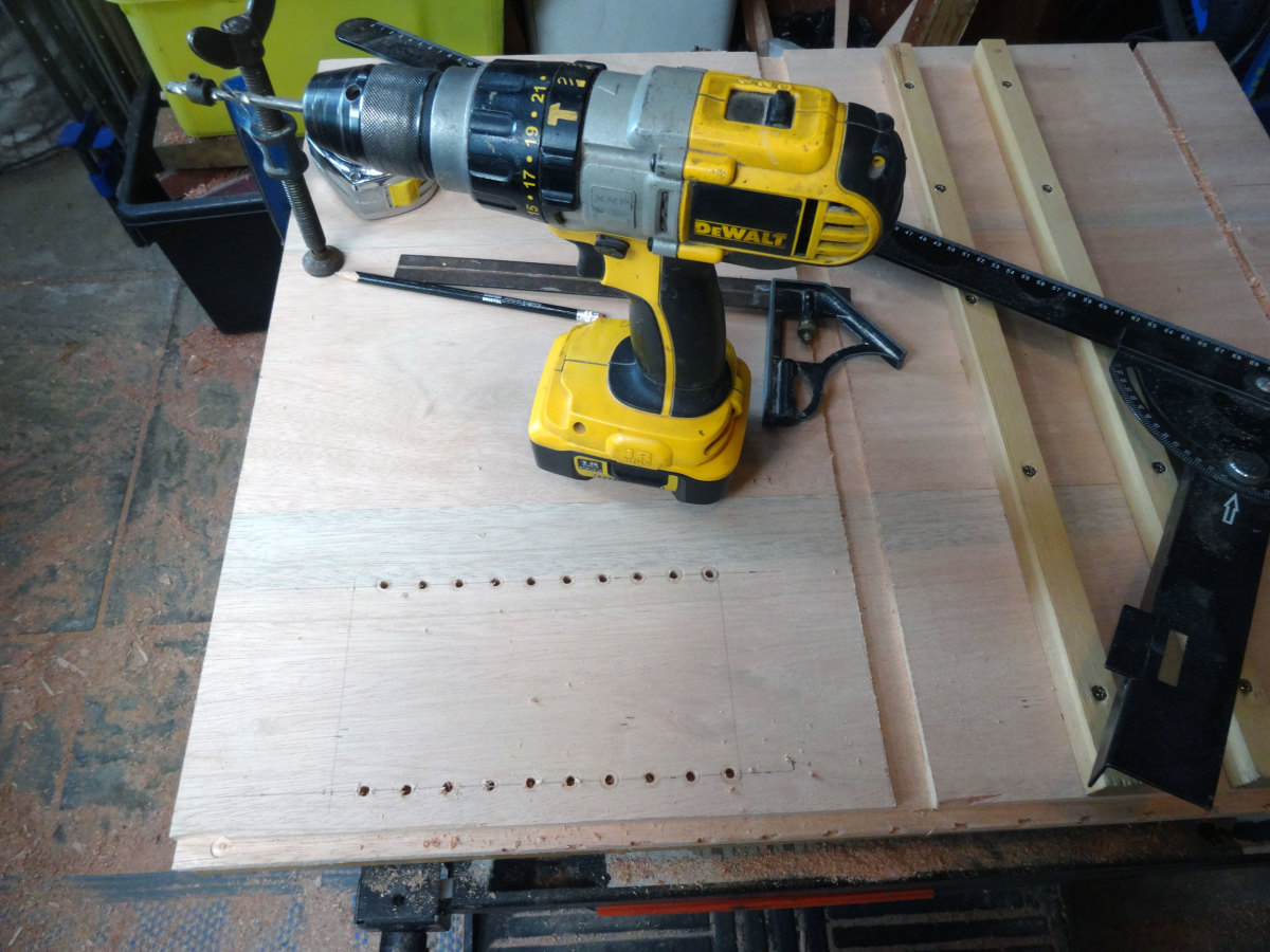 Drilling the holes in the side panels for the adjustable shelves