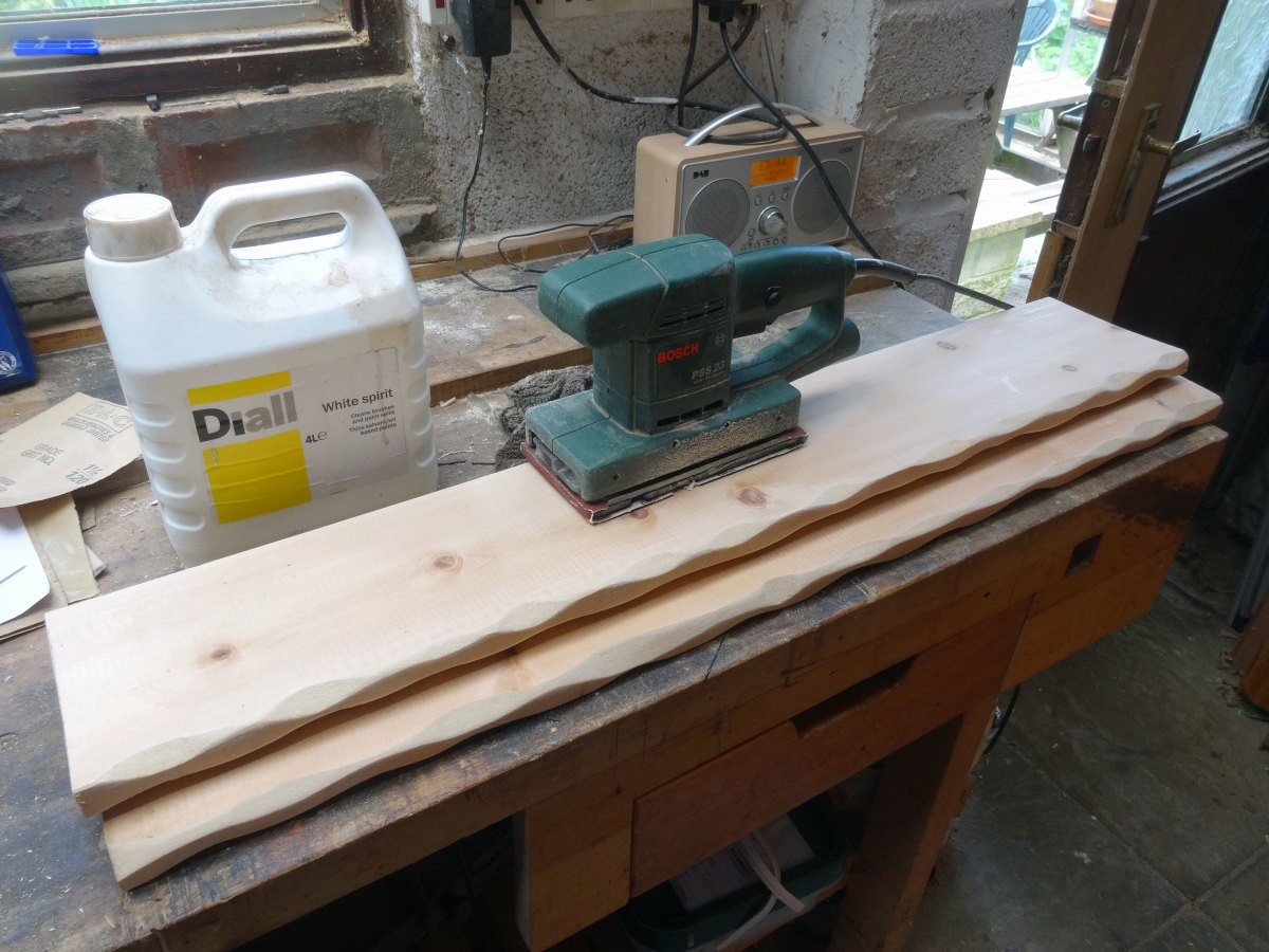 Sanding shelves and hewed edges smooth with an orbital sander.