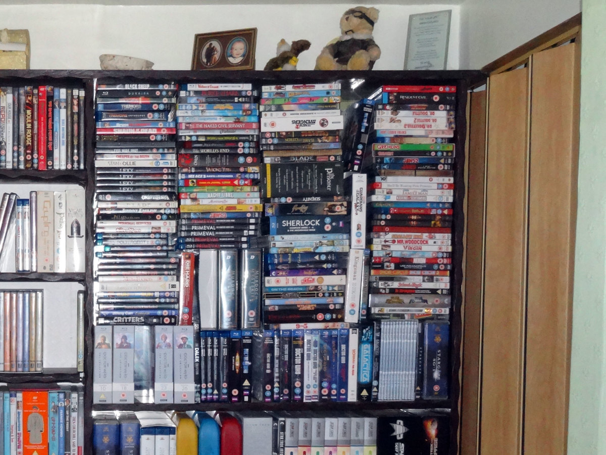 DVDs and Blu-ray discs stacked on top of each other in the top right hand corner, hence the need for additional shelving.