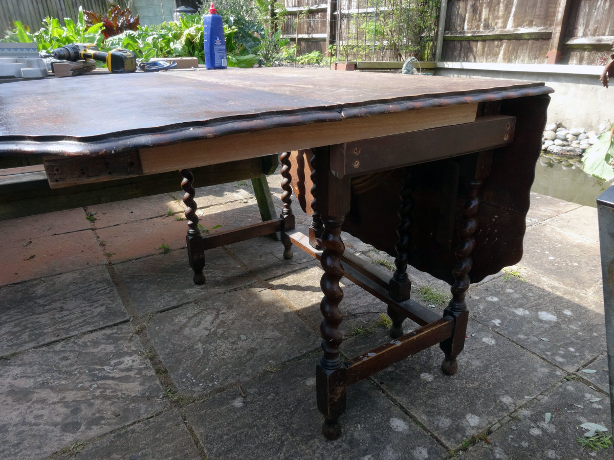 Arm slid in place, to support the drop leaf table top, and supported by the arm support fitted to the table's side skirt.