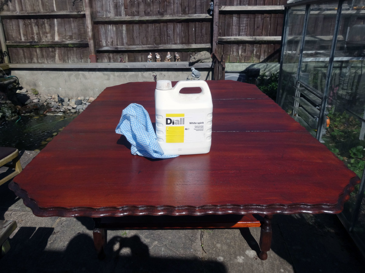 Cleaning table top with white spirit after light hand sanding, prior to applying final coat of wood stain.