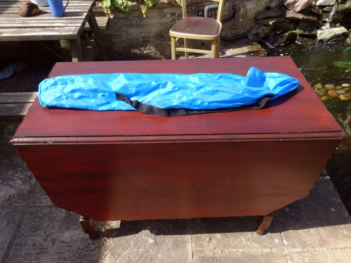 Redundant blue carry bag for broken folding chair repurposed as storage bag for the removable table arms and Chrome legs for drop leaf table top support.
