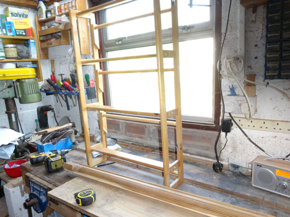 Redundant shoe rack on workbench, with other scrap wood, ready for salvaging to recycle into table shelf.
