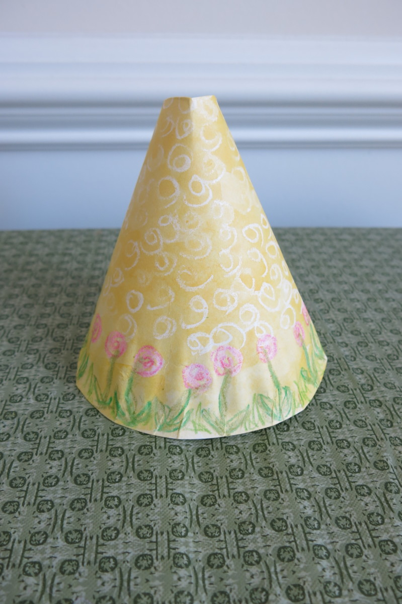 Form the decorated paper plate into a cone to make the bunny's body.
