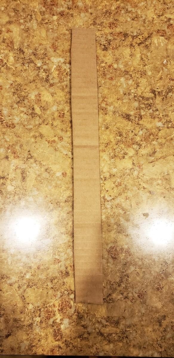 Cut a long, rectangular strip from cardboard.
