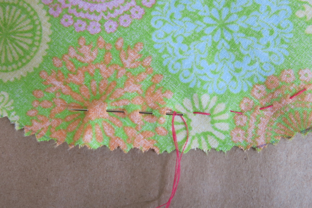 Running stitch around the fabric to gather it for the top of your pincushion
