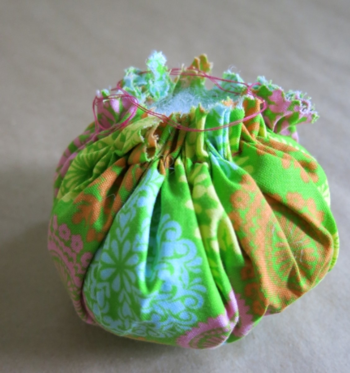 Gathering your fabric and adding stuffing to make the top of your pincushion.