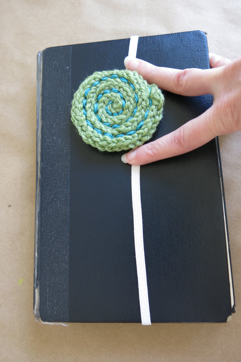 Measuring your elastic for your knitted yarn ball bookmark.