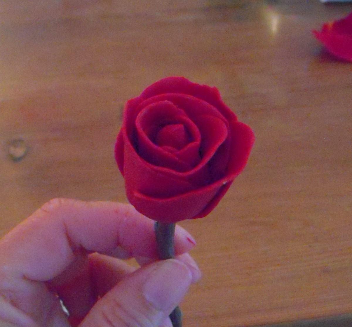 With all petals wrapped, slightly curl outward the edge of last petal so that it looks like the rose is blooming.