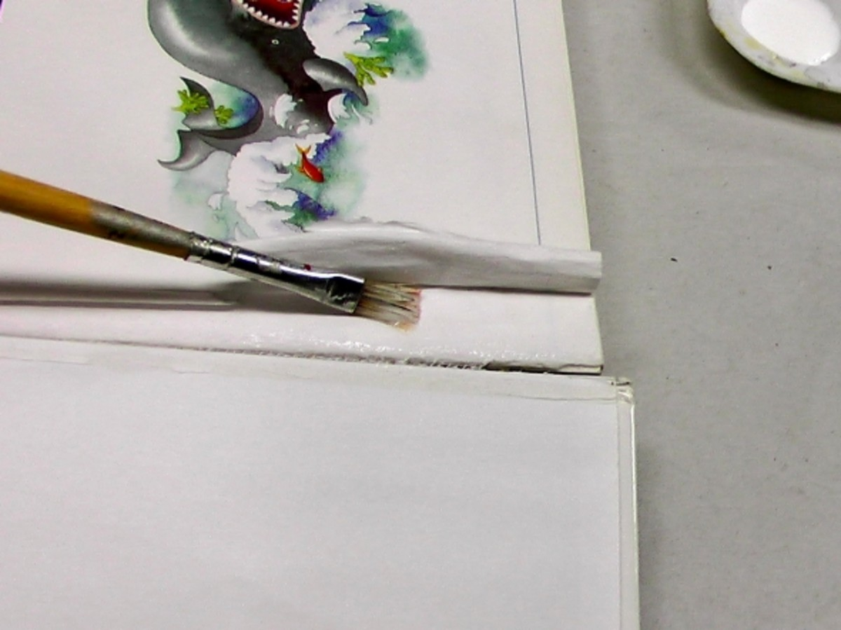 Applying glue with a brush to a book's spine. I used a small, flat brush to apply the PVA glue.