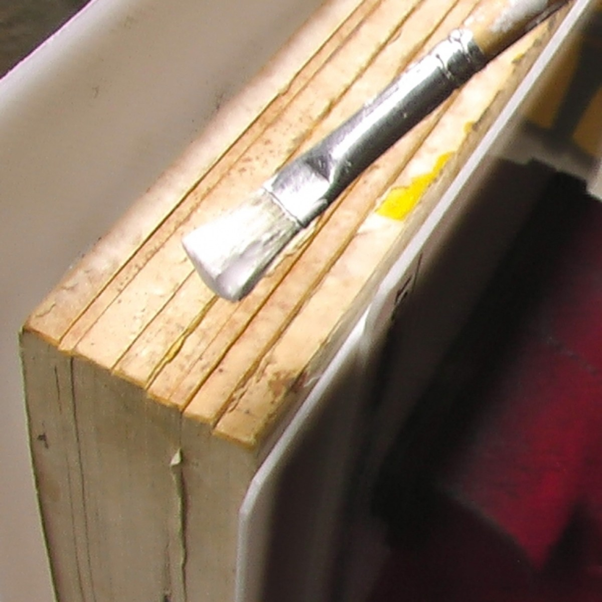 Gluing the separated signatures of a paperback cookbook. Notice how the signatures have been separated due to time and use. I am using Brodart glue.
