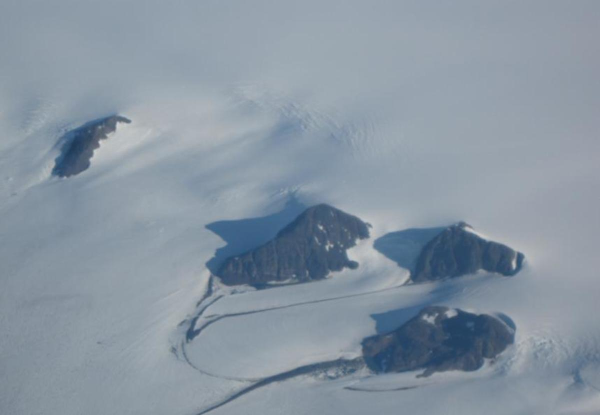 Aerial photo of Mountain Peaks protruding above the Greenland ice cap.