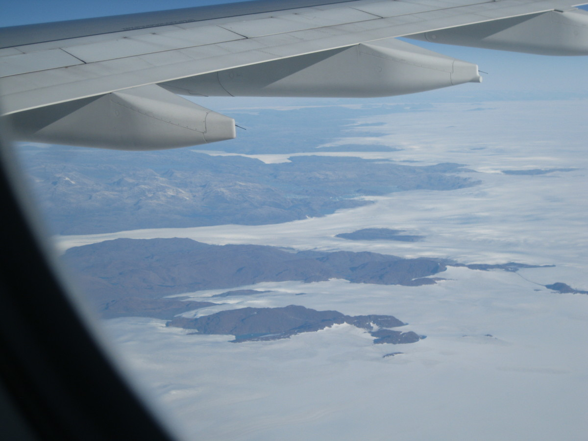 Mountains and lakes in southern Greenland  beneath the wing of a jet liner.