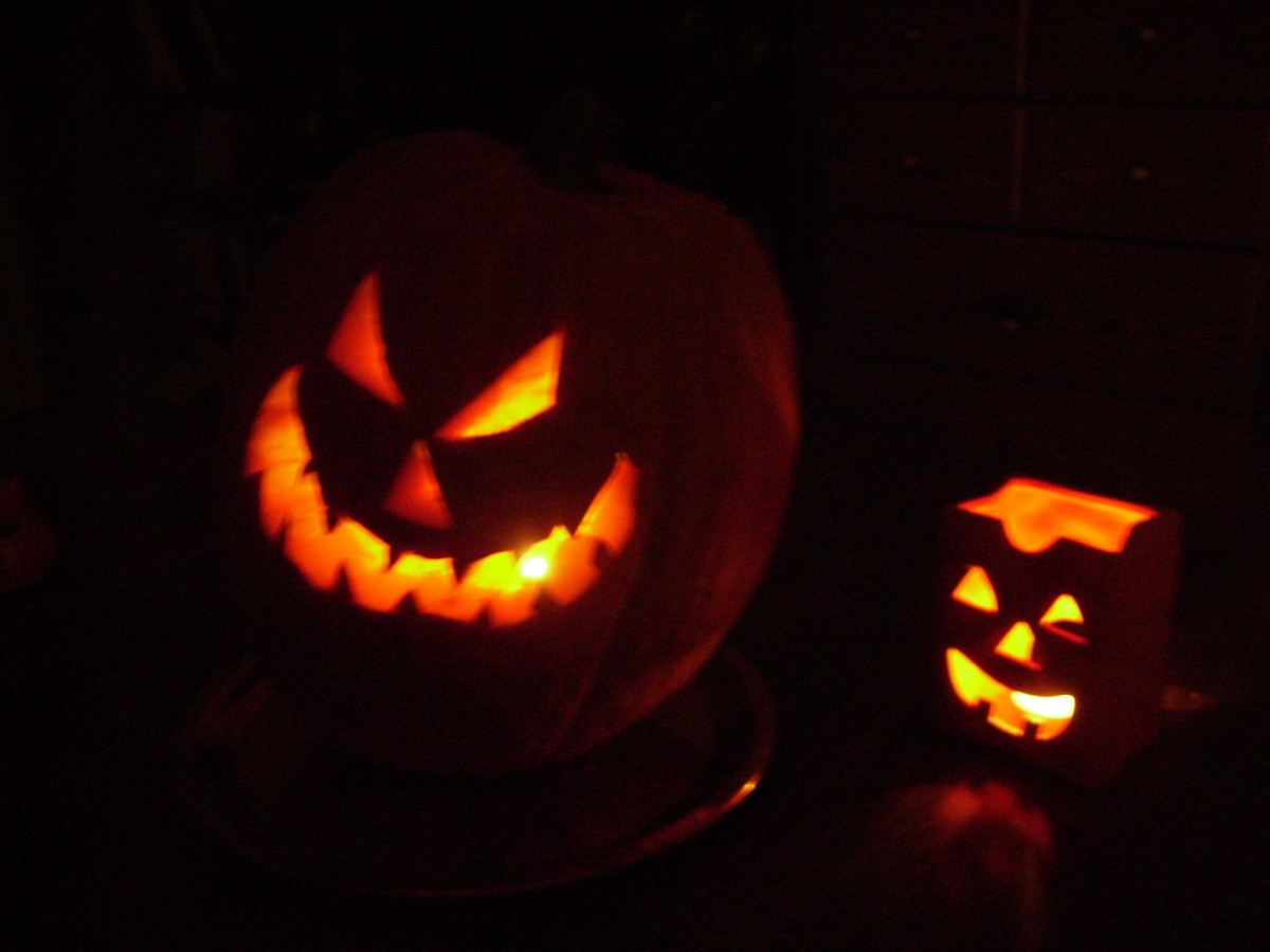 Two scary Halloween Jack-O-Lanterns glowing in the dark