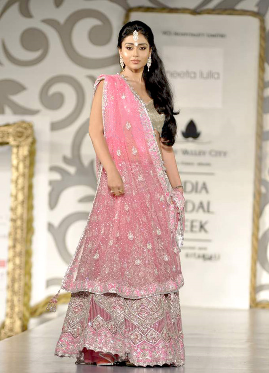 Actress Shriya Saran modeling a fully embroidered pink Ghagra Choli worn during marriage ceremonies.