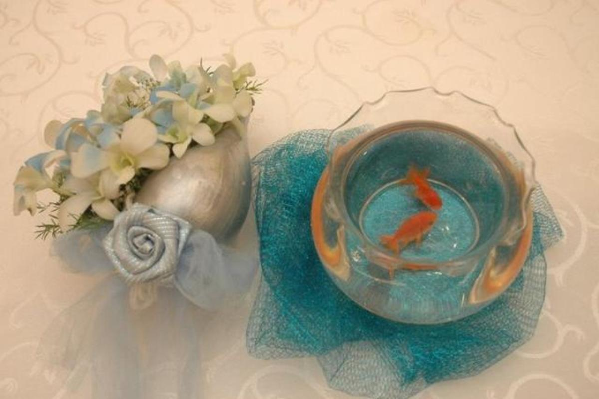 A fish bowl and shell flower vase for each individual wedding reception dinner table.