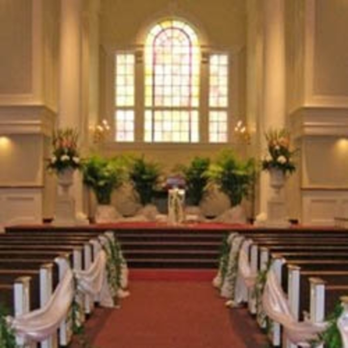 Church decorated for a wedding with pew swags, rented plants, and a couple of altar arrangements