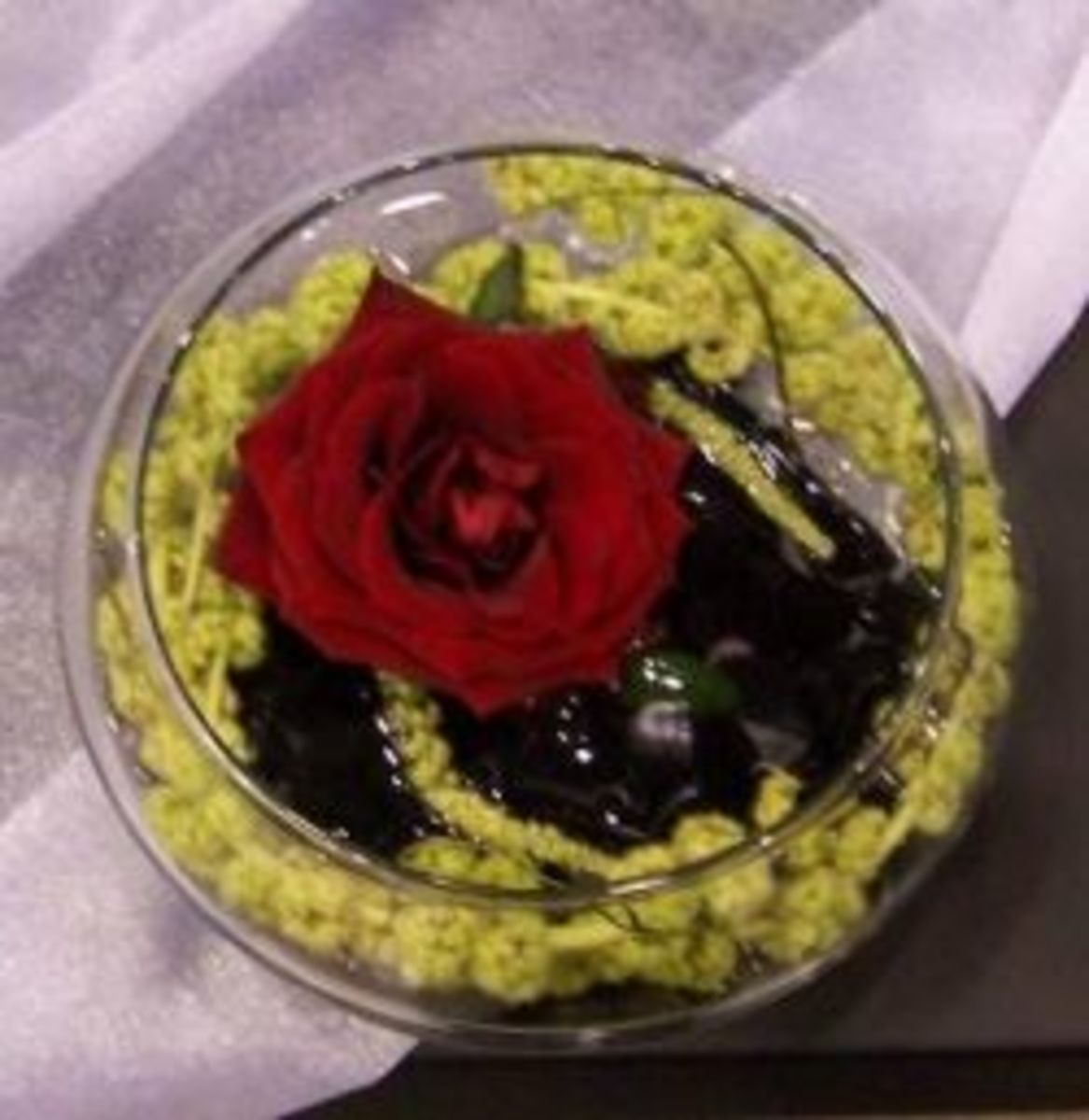 Grand Prix rose with green amaranthus in a shallow glass bowl.