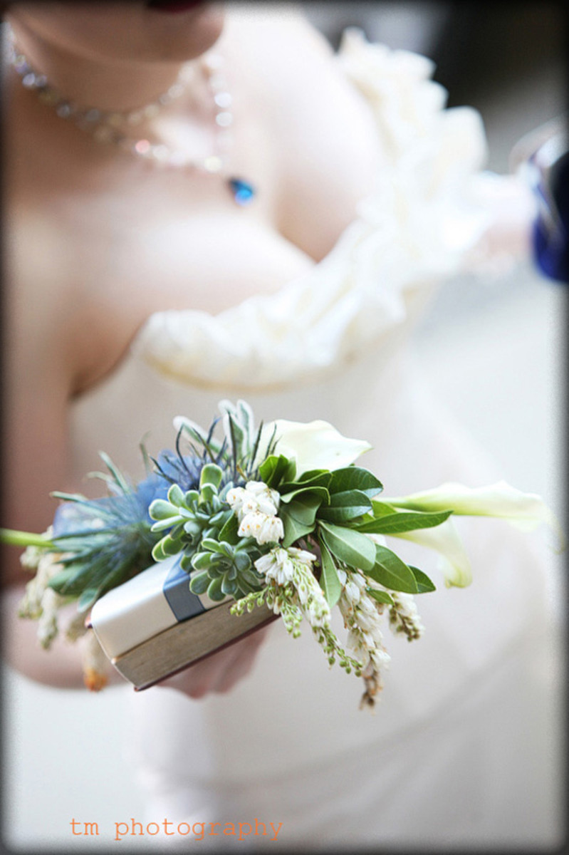 A white family Bible with flowers is an alternative to a bouquet for Catholic brides.