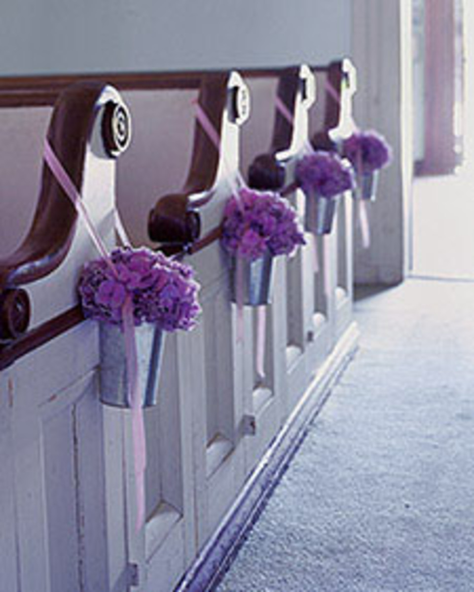 Metal sap buckets filled with flowers and hung by ribbon.