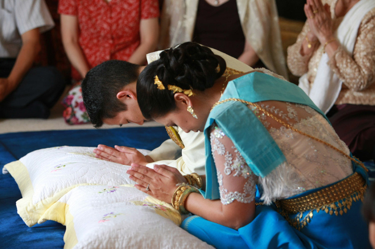 The couple remains quiet, with their heads bowed and hands in prayer.