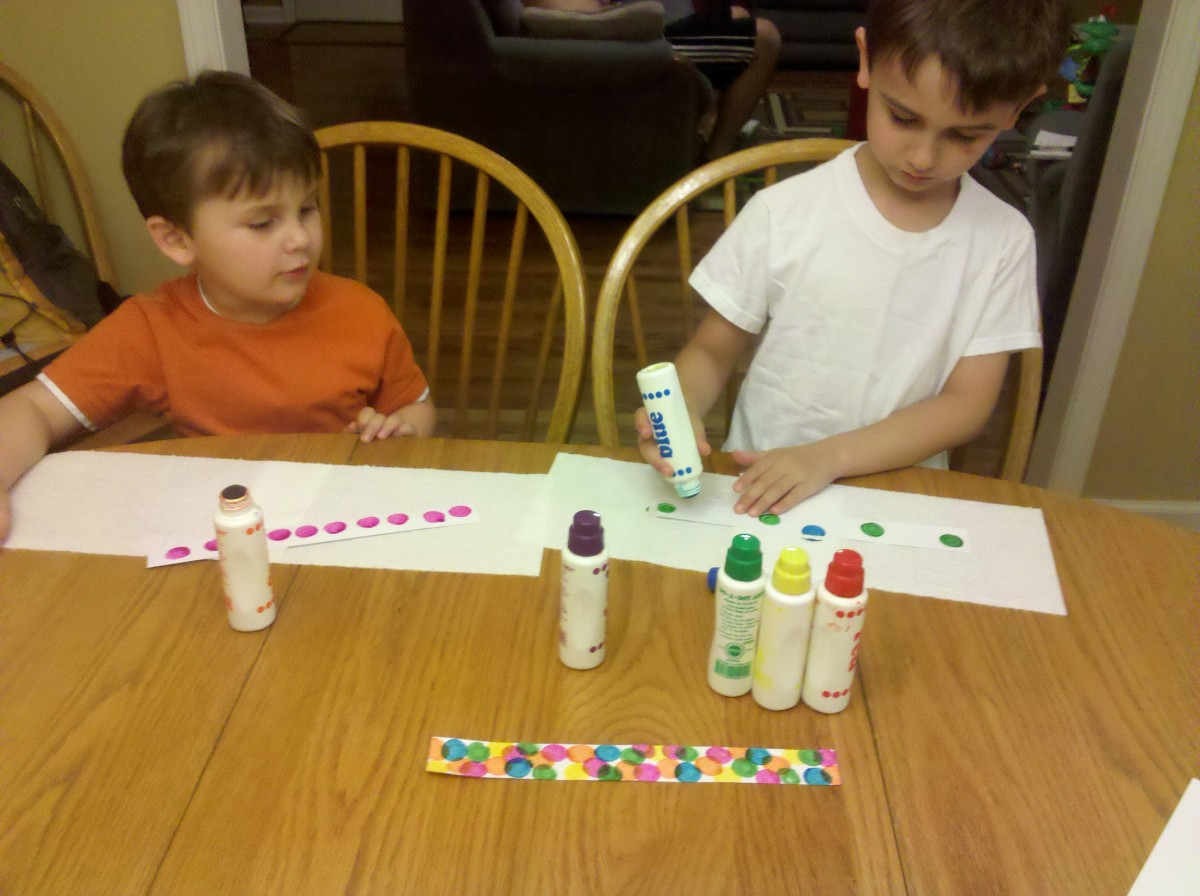 My sons painting their cupcake wrappers with Do-A-Dot bottles.