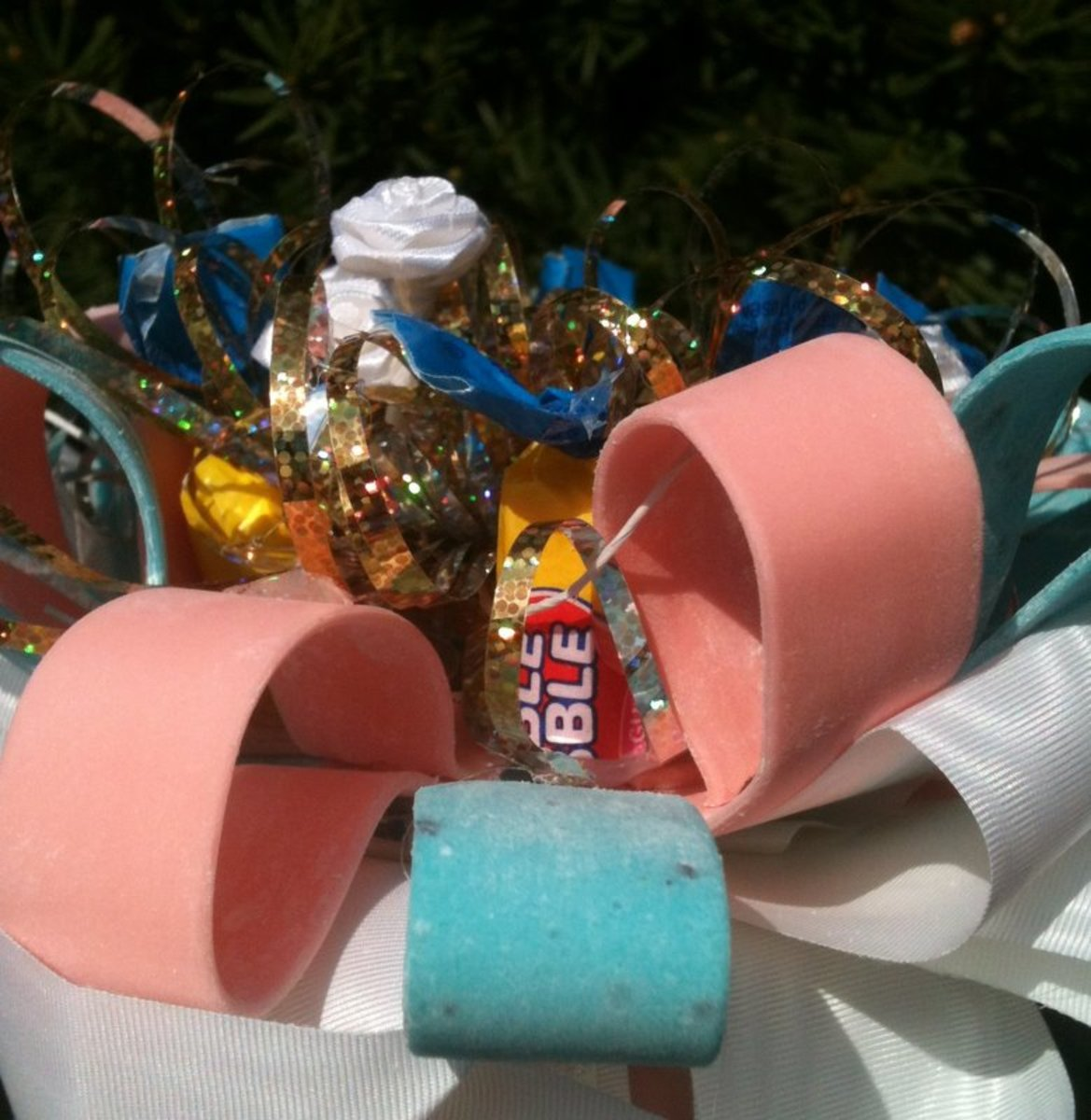 "A close-up, inside view of the candy corsage showing the tape and tube forms of bubble gum, tiny white silk flowers, satin ribbon, and a recycled metallic ""fountain"" bow."