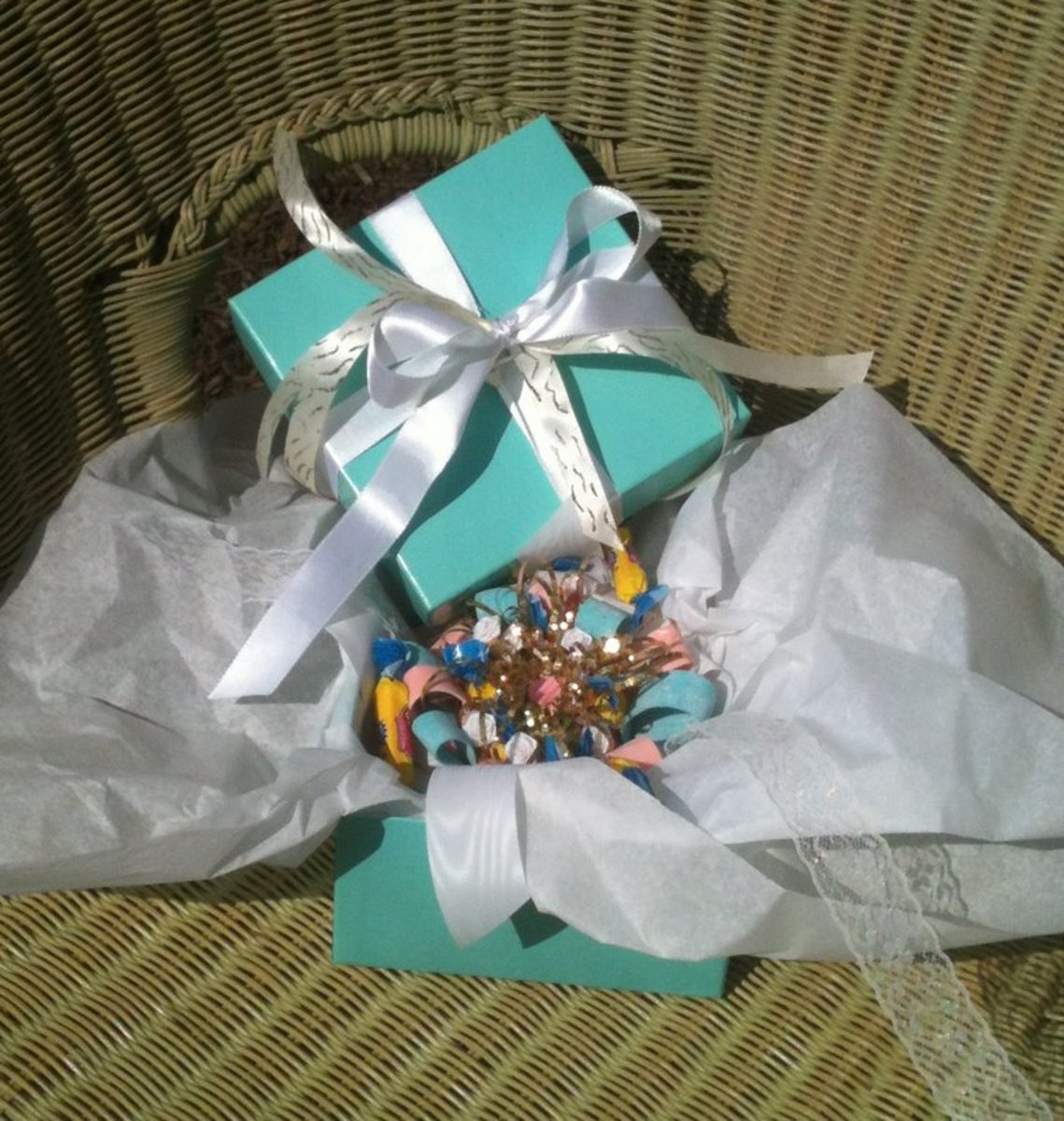 The long lace pieces of ribbon were tied into a bow, securing the corsage on the wrist. White tissue paper protected the corsage inside the white and gold-ribboned box.