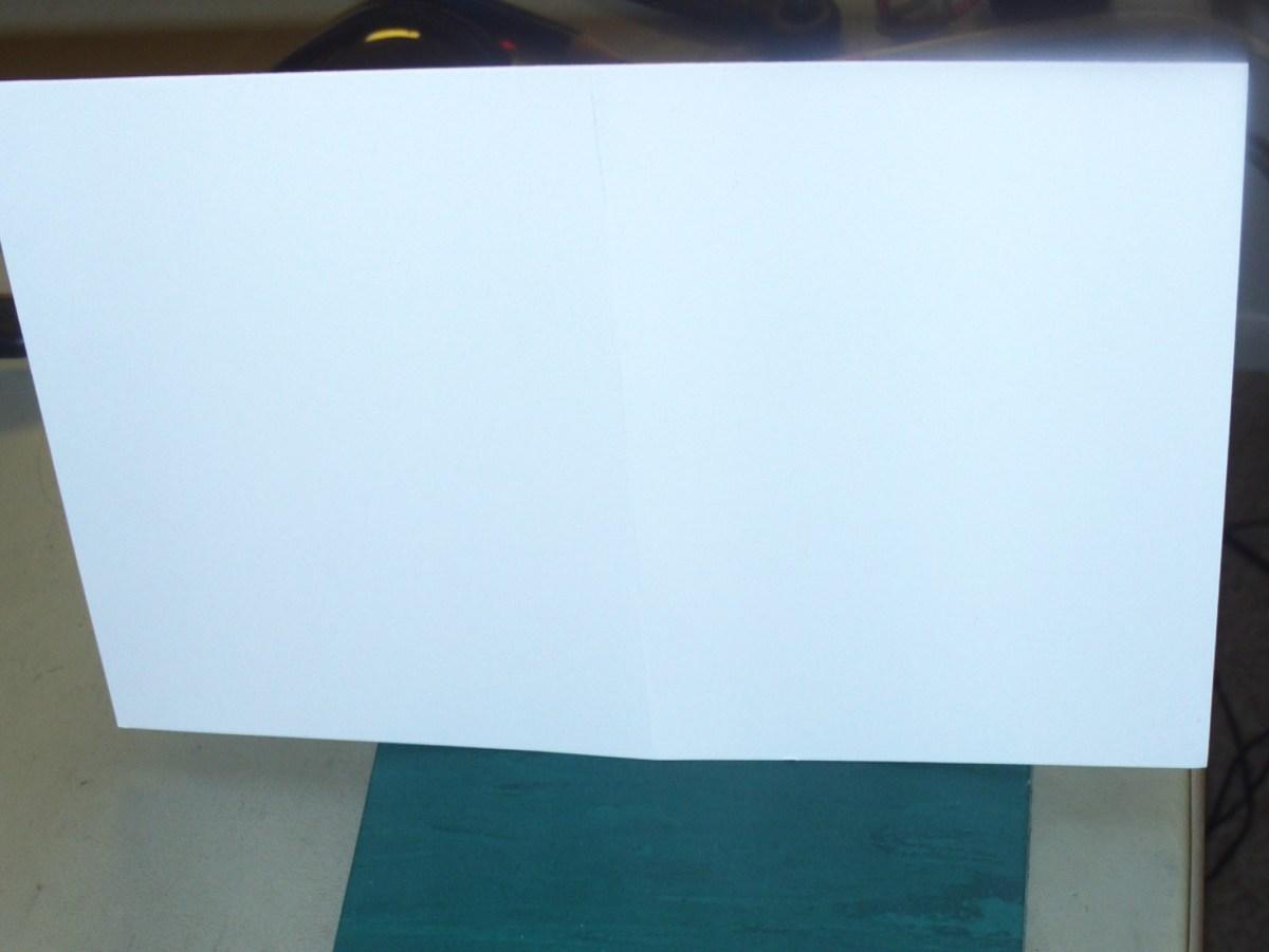 Fold the sheet of card stock in half to make a half-fold card.