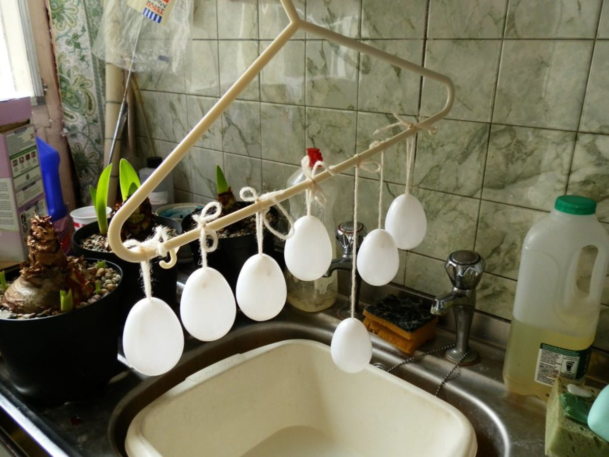 plastic Easter eggs covered with egg white, hanging up to dry