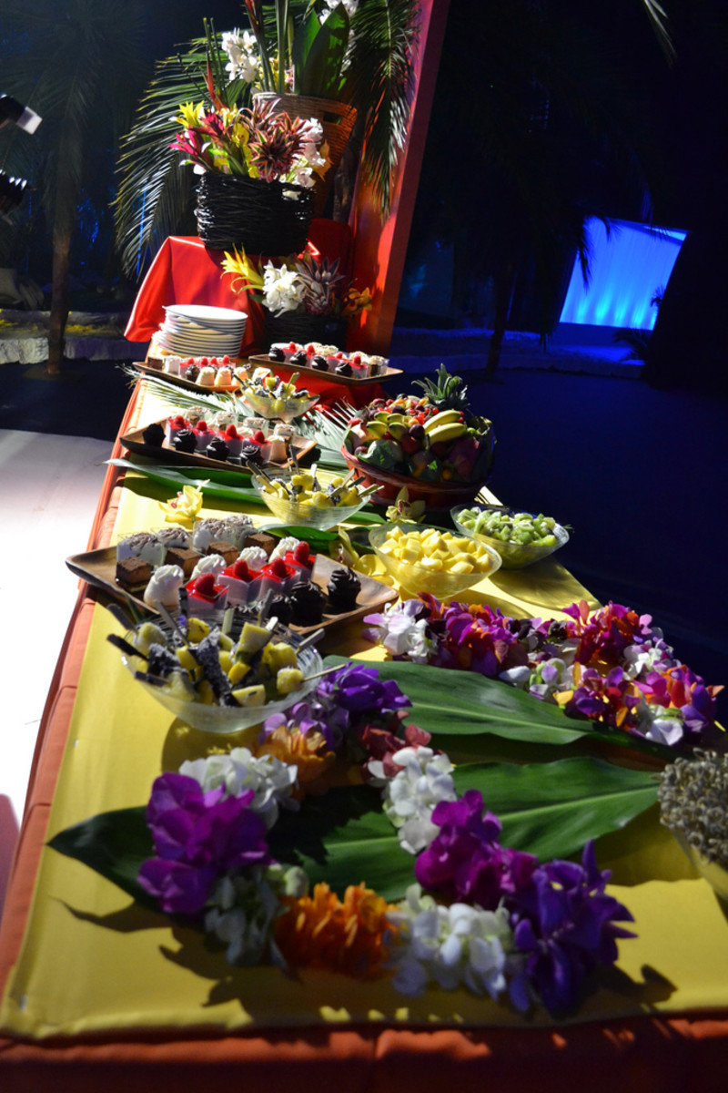 Buffet of food with lots of fruit and flowers for decoration.