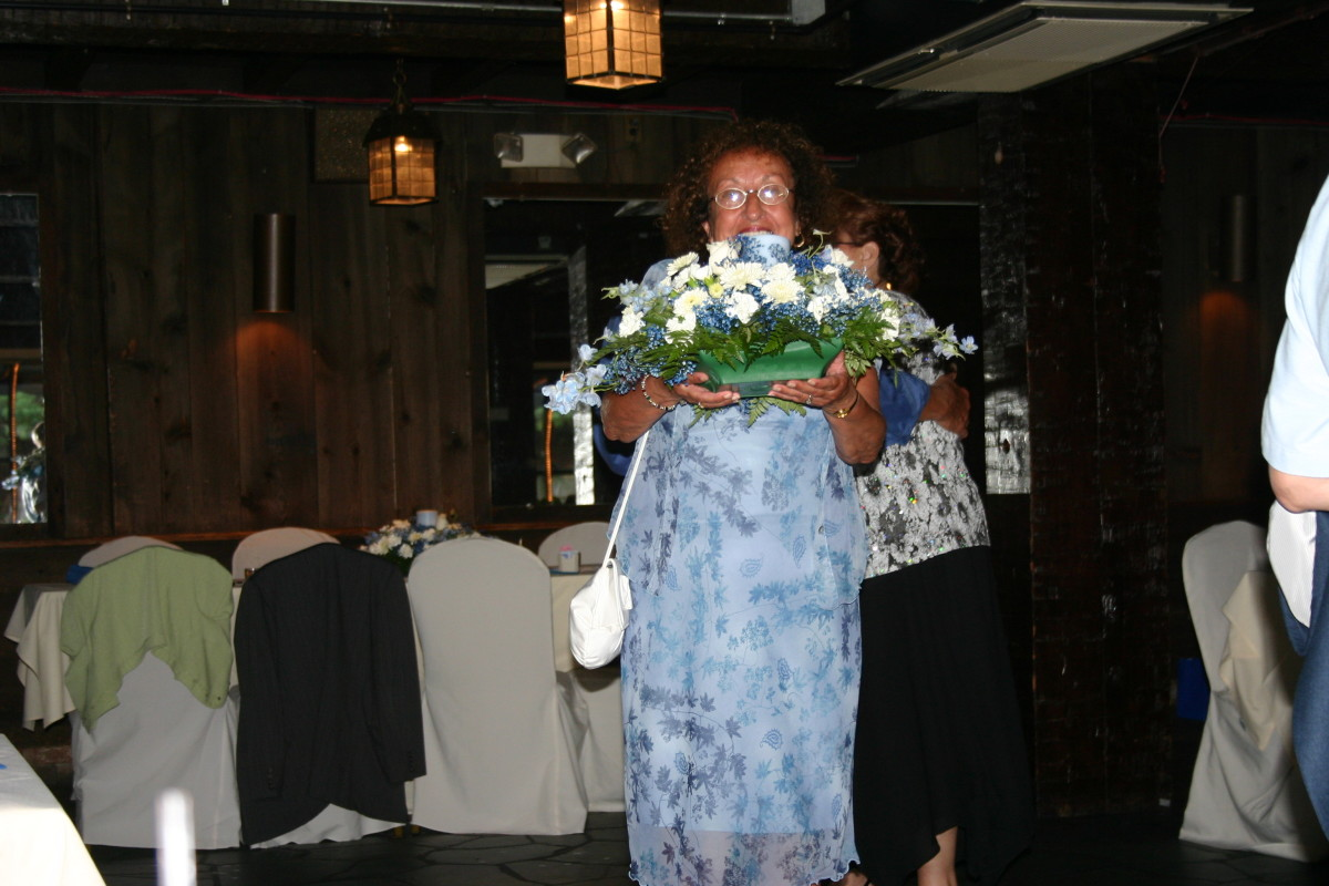 A happy Wedding Reception Trivia Game winner taking her prize centerpiece home at the end of the reception!