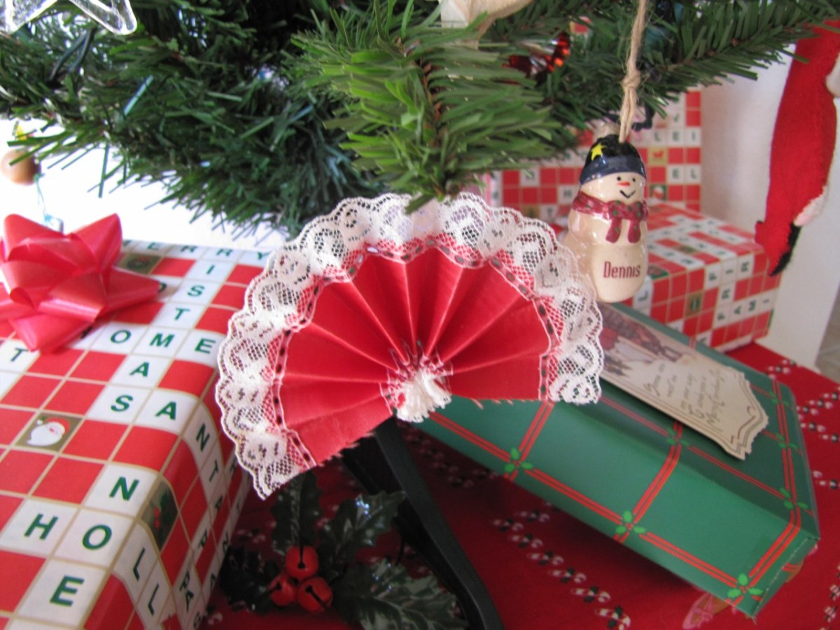 A fan ornament made from red lace-trimmed ribbon.