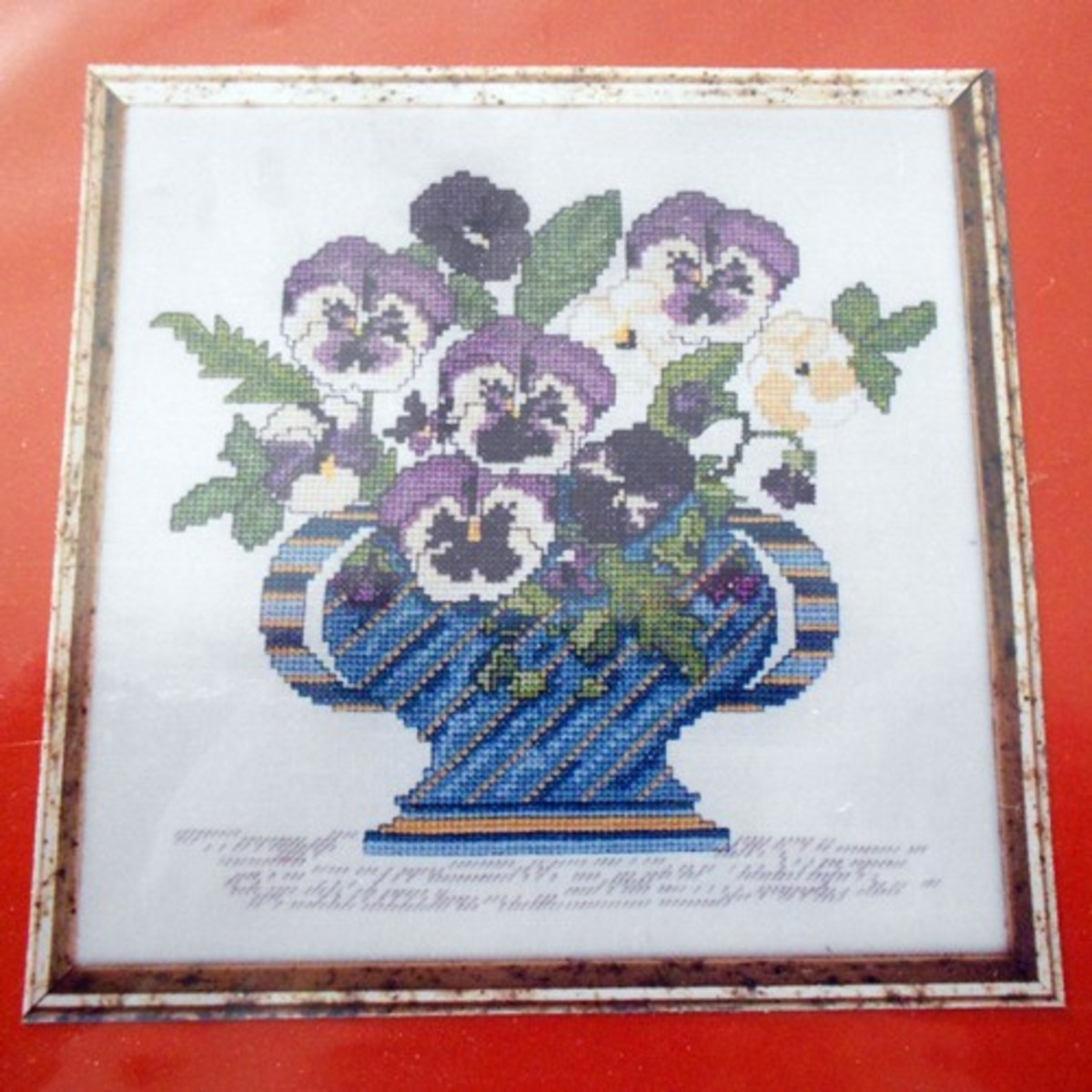 This cross-stitch showcases the traditional pansy flower.