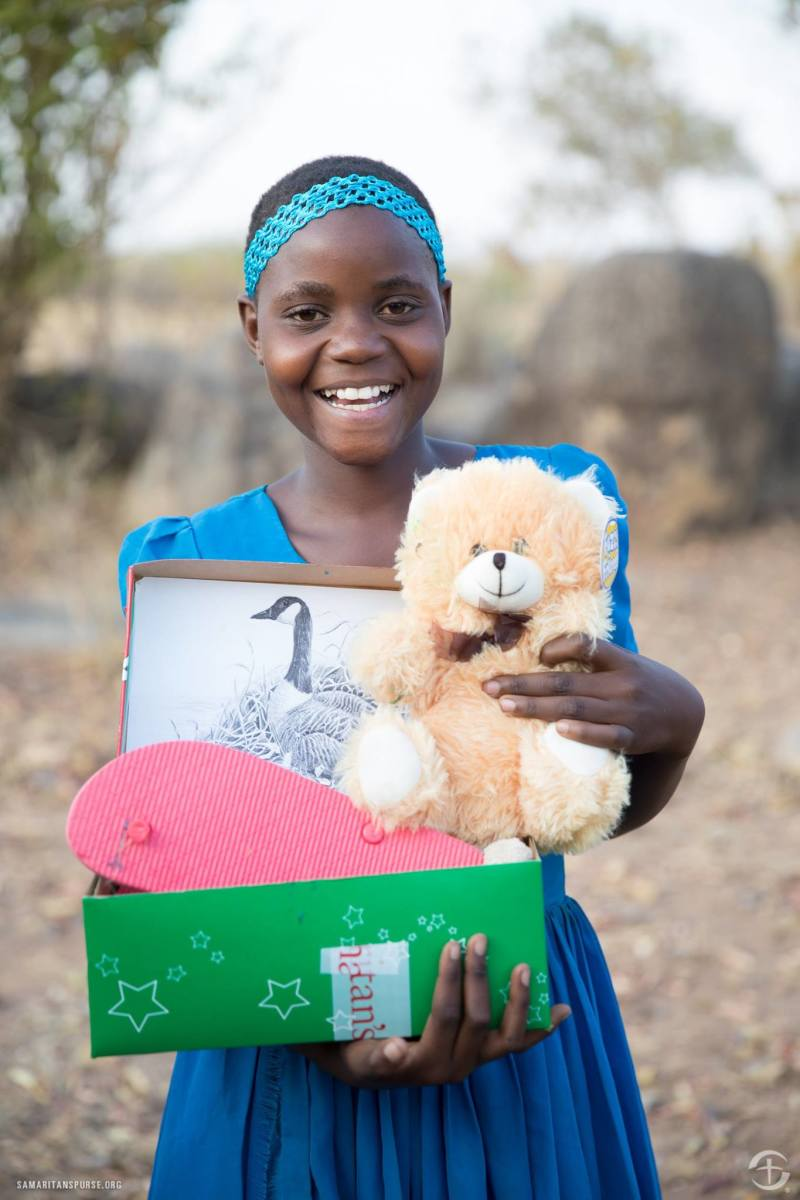 A girl showing off her new stuffed animal and flip flops in Tanzania.