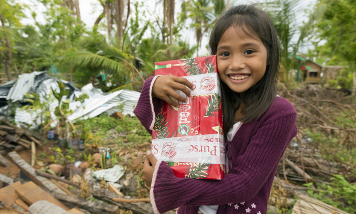 A girl hugging her shoebox in the Philippines.