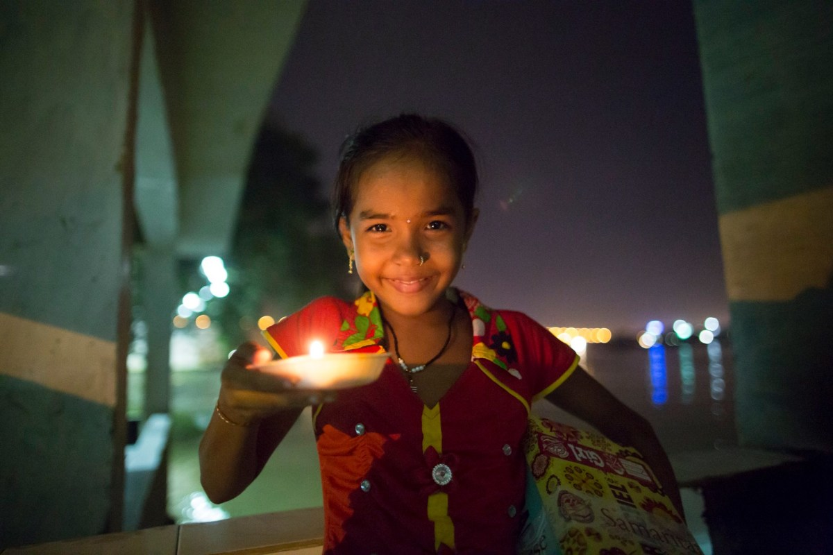 A girl lights the way with a candle while carrying her shoebox home in a village where electricity is scarce and unreliable.