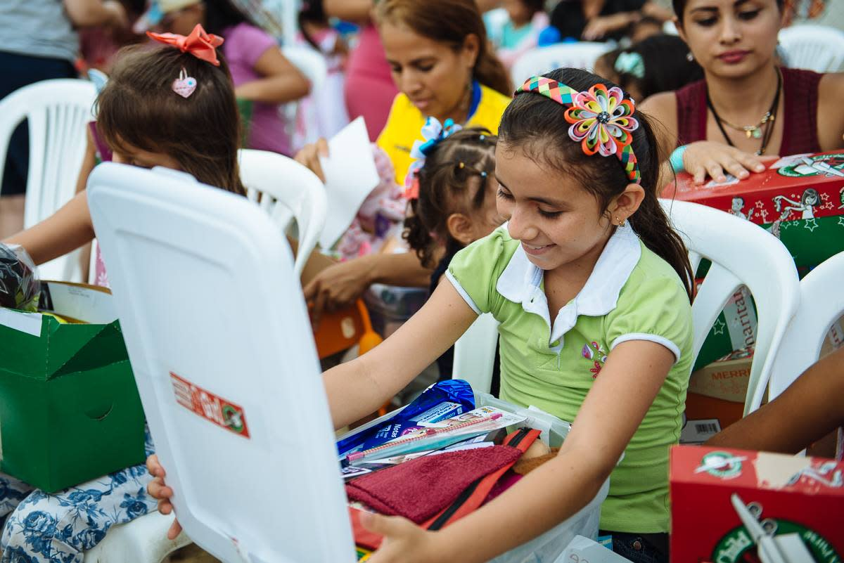 A girl opening her shoebox in Ecuador.