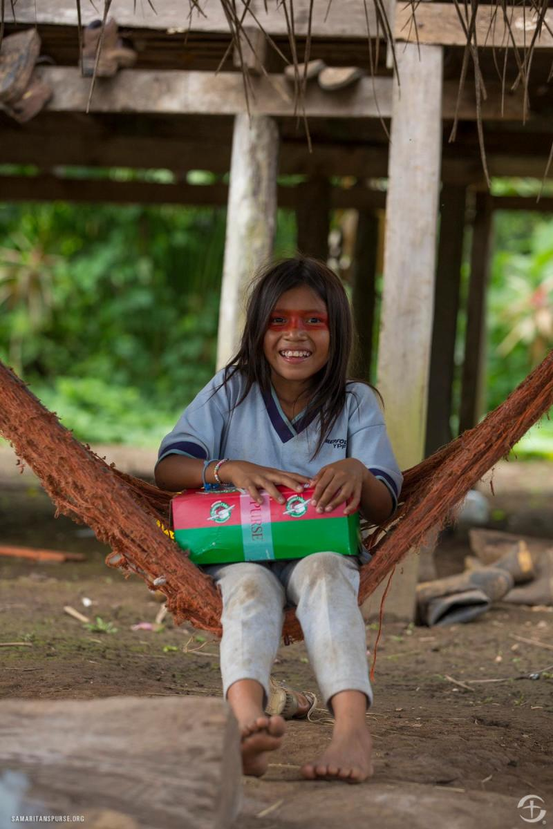 A girl in a hammock holding her shoebox in Ecuador.
